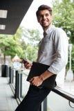 Homme d'affaires tenant le dossier et à l'aide du téléphone portable dehors photo libre de droits