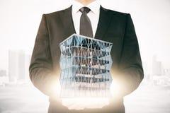 Homme d'affaires tenant le gratte-ciel Images stock
