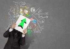 Homme d'affaires tenant le livre avec le vert vers le haut de la flèche Image stock