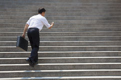 Homme d'affaires tenant le mobile et dans la hâte pour courir sur des escaliers photographie stock libre de droits