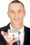 Homme d'affaires tenant le modèle de maison Photographie stock libre de droits