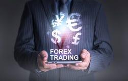 Homme d'affaires tenant le monde de comprimé du commerce de forex de devise Photographie stock libre de droits