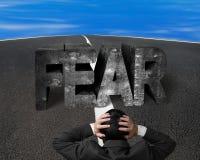 Homme d'affaires tenant le mot concret de crainte principale de revêtement sur le RO d'asphalte Photographie stock