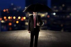 Homme d'affaires tenant le parapluie se tenant sur le dessus de toit Photographie stock libre de droits