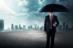 Homme d'affaires tenant le parapluie se tenant sur le dessus de toit Images stock