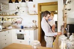Homme d'affaires tenant le petit fils dans les bras, préparant le café Images libres de droits