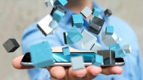 Homme d'affaires tenant le renderin brillant bleu de flottement du réseau 3D de cube Photographie stock