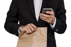 Homme d'affaires tenant le sac de papier brun, et à l'aide du téléphone intelligent, d'isolement sur le fond blanc Images stock