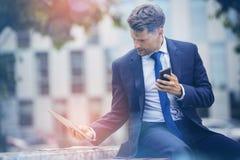 Homme d'affaires tenant le téléphone portable tout en à l'aide du comprimé numérique sur le mur de soutènement Photographie stock libre de droits