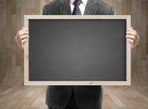 Homme d'affaires tenant le tableau noir Images stock