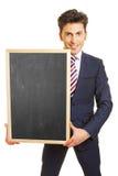 Homme d'affaires tenant le tableau noir vide Photos stock