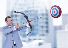 Homme d'affaires tenant le tir à l'arc tout en visant le panneau de cible Images libres de droits