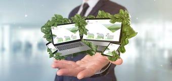 Homme d'affaires tenant les dispositifs reliés entourant par le rendu des feuilles 3d photographie stock