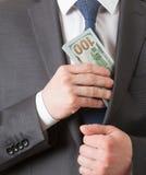 Homme d'affaires tenant les dollars/mettant des dollars dans une poche Photo stock