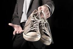 Homme d'affaires tenant les espadrilles sales Image libre de droits