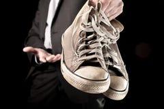 Homme d'affaires tenant les espadrilles sales Image stock