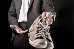 Homme d'affaires tenant les espadrilles sales Photographie stock libre de droits
