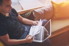 Homme d'affaires tenant les papiers et l'ordinateur portable photo stock