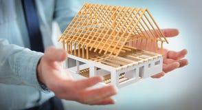 Homme d'affaires tenant 3D rendant la maison non finie de plan dans son ha Image libre de droits