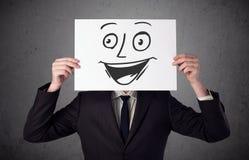 Homme d'affaires tenant un carton avec le visage souriant là-dessus dans l'avant Photos libres de droits