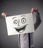 Homme d'affaires tenant un carton avec le visage souriant là-dessus dans l'avant Photo libre de droits
