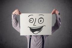 Homme d'affaires tenant un carton avec le visage souriant là-dessus dans l'avant Photographie stock libre de droits