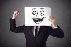 Homme d'affaires tenant un carton avec le visage souriant là-dessus dans l'avant Images libres de droits