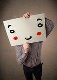 Homme d'affaires tenant un carton avec un visage souriant là-dessus Image stock