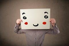Homme d'affaires tenant un carton avec un visage souriant là-dessus Images stock