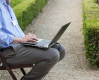 Homme d'affaires tenant un ordinateur portable sur ses genoux Images libres de droits