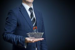 Homme d'affaires tenant un panier à provisions sur sa main images stock