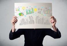 Homme d'affaires tenant un papier avec des diagrammes et le paysage urbain en o avant Photo stock
