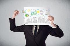 Homme d'affaires tenant un papier avec des diagrammes et le paysage urbain en o avant Photographie stock libre de droits