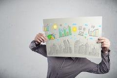 Homme d'affaires tenant un papier avec des diagrammes et le paysage urbain en o avant Image stock