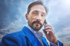 Homme d'affaires tenant un smartphone, portrait, jour, extérieur photographie stock libre de droits