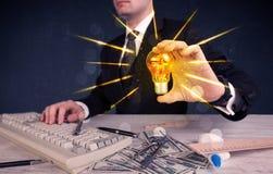 Homme d'affaires tenant une ampoule électrique Images stock