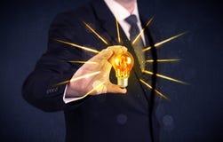 Homme d'affaires tenant une ampoule électrique Image stock