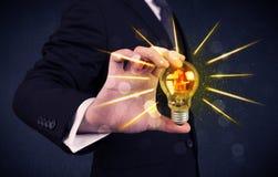 Homme d'affaires tenant une ampoule électrique Images libres de droits