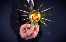 Homme d'affaires tenant une ampoule électrique Image libre de droits