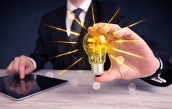 Homme d'affaires tenant une ampoule électrique Photo libre de droits
