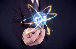 Homme d'affaires tenant une ampoule colorée images stock