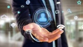 Homme d'affaires tenant une icône de contact entourant par APP et social Photographie stock