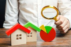 Homme d'affaires tenant une loupe au-dessus d'un graphique circulaire et maisons en bois Analyse de concept du march? de l'immobi photographie stock
