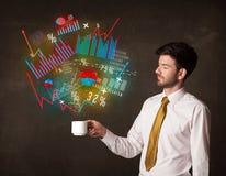 Homme d'affaires tenant une tasse blanche avec des diagrammes et des graphiques Images libres de droits