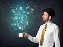 Homme d'affaires tenant une tasse blanche avec des icônes d'affaires Images stock