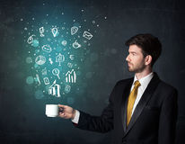 Homme d'affaires tenant une tasse blanche avec des icônes d'affaires Photo stock