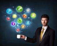 Homme d'affaires tenant une tasse blanche avec des icônes d'arrangement Image stock