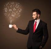 Homme d'affaires tenant une tasse blanche avec les icônes sociales de media Photos stock