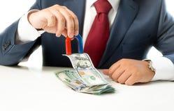 Homme d'affaires tirant l'argent de la pile sur la table avec l'aimant Photo stock