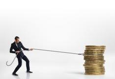 Homme d'affaires tirant la pile de grandes pièces de monnaie d'or avec une corde sur le fond blanc images libres de droits